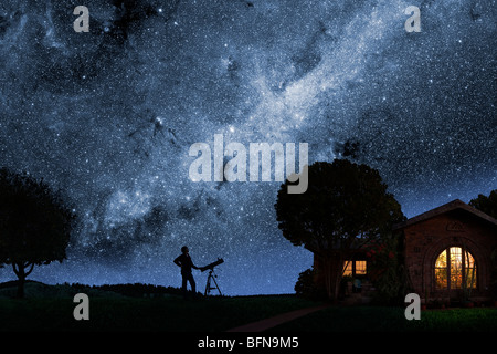 A man gazes at the Milky Way outside his house at night - Stock Photo