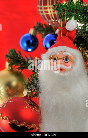 Santa Claus / Father Christmas and bells hanging in tree - Stock Photo