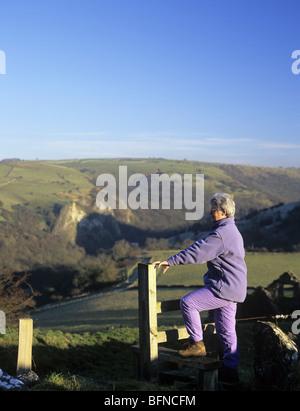 Grindon, Staffordshire, England, UK. Senior woman walker climbing over stile overlooking the Manifold Valley. - Stock Photo
