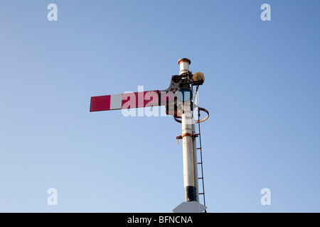 Railway semaphore stop signal in the on position in North Wales station - Stock Photo