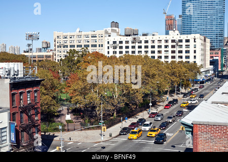 looking North down on 11th Avenue toward DeWitt Clinton park on sunny autumn afternoon with bright foliage & old - Stock Photo