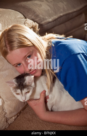 Junior high girl 11-12 year years old cuddling her cat. California  2009  MR © Myrleen Pearson - Stock Photo