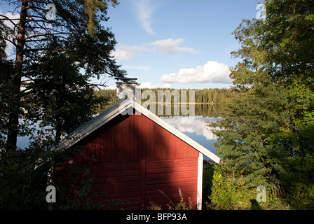 Red cabin by a lake , Finland - Stock Photo
