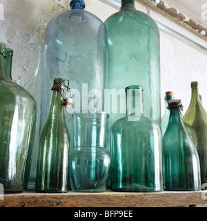 Row of assorted antique bottles and glassware on shelf / ledge - Stock Photo