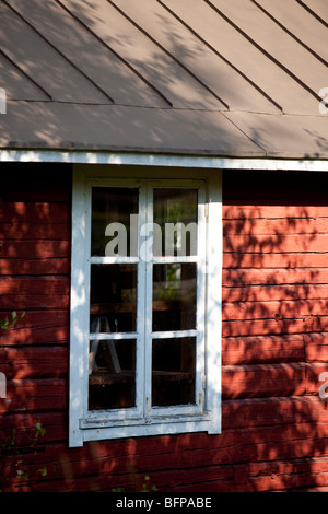 Window in red ochre painted log cabin wall - Stock Photo