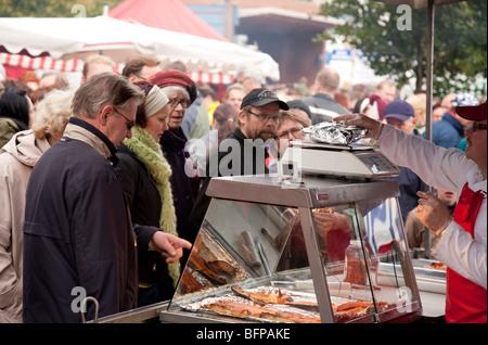 Customers buying freshly cooked fish at Kalaryssäys Kalaryssaeys market fair in Kuopio City Finland - Stock Photo