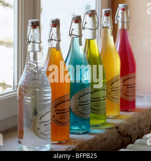Row of glass bottles filled with multicoloured liquids on windowsill / ledge - Stock Photo