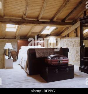 Bedroom in 17th century barn renovation with original oak rafters