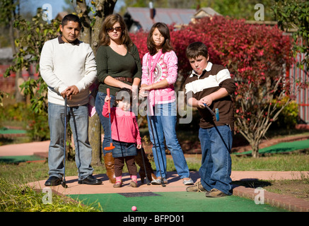 A mixed-race family participates in a round of miniature golf. - Stock Photo