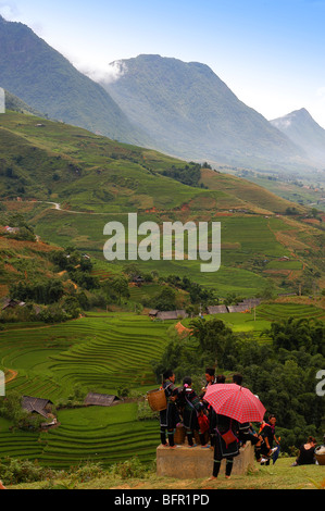View across a terraced valley of paddy fields towards mountains that surround Sa Pa, a market town in northwest - Stock Photo