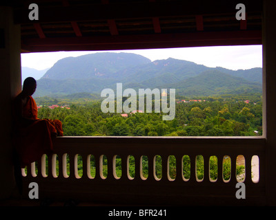 Monk admiring the view from the hill side Buddhist temple on Mount Phu Si in the centre of old town Luang Prabang - Stock Photo
