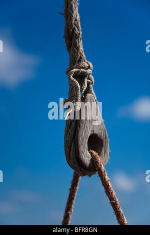 Knotted rope on a wooden pulley of a dhow - Stock Photo