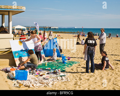 Artists and families painting a mural of the shoreline during the Bournemouth Beach Festival. Dorset. UK. - Stock Photo