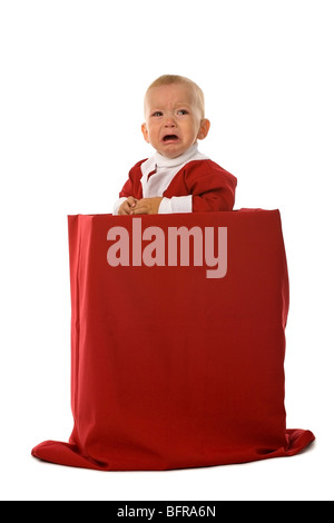 crying little boy in red Santa Claus clothes standing in big box with christmas gifts, isolated on white - Stock Photo