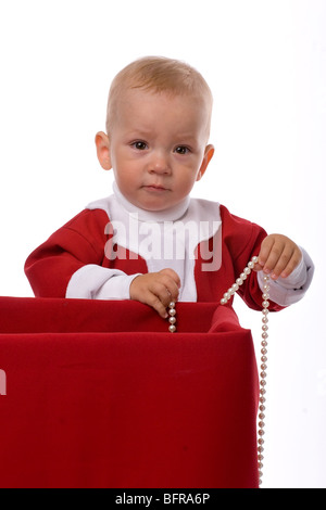 funny little boy in red Santa Claus clothes standing with pearl necklace near big box with christmas gifts, isolated - Stock Photo