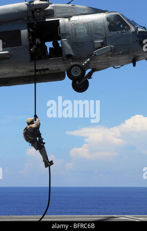 An explosive ordnance disposal technician fast ropes onto the flight deck of the USS Ronald Reagan. - Stock Photo