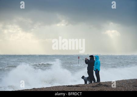 Couple and dog taking photograph of storm. Sandgate, Kent, UK - Stock Photo