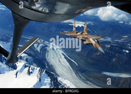 A U.S. Air Force F-15C Eagle positioning itself behind a KC-135R Stratotanker over Alaska. - Stock Photo