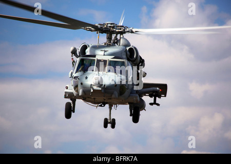 Navy pilots in a SH-60F Seahawk conduct final approach for landing. - Stock Photo