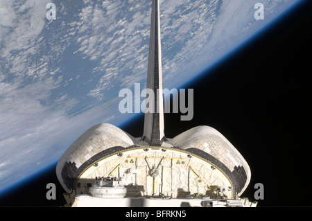 A partial view of Space Shuttle Endeavour backdropped by Earth's horizon. - Stock Photo