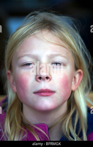 A pale, rosy cheeked six year old girl making faces. - Stock Photo