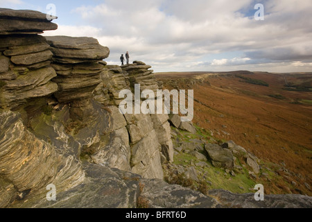 Two Walkers admiring the view from Stanage Edge, near Hathersage in the Derbyshire Peak District, UK - Stock Photo
