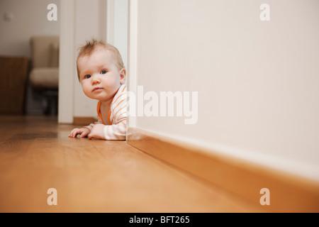 Baby Lying on Floor Peeking Around a Corner - Stock Photo