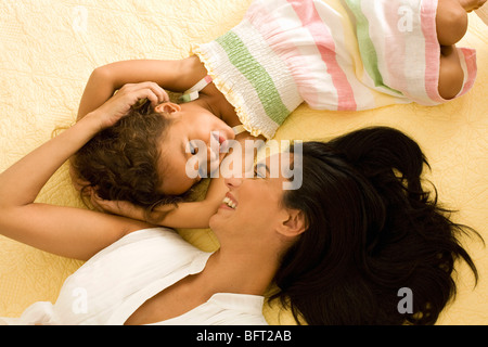 Mother and Daughter Lying on Bed Together - Stock Photo