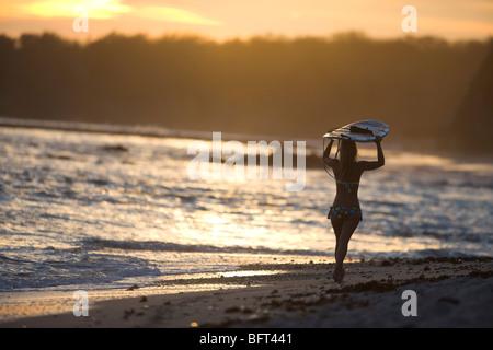 Surfer Walking on the Beach, Punta Burros, Nayarit, Mexico - Stock Photo
