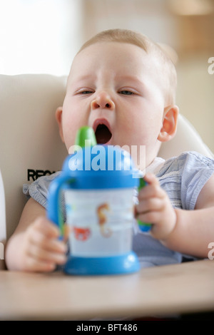 Baby Girl in High Chair Yawning - Stock Photo