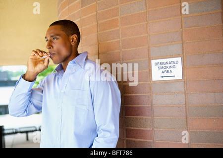 Man Smoking a Cigarette in Designated Area - Stock Photo
