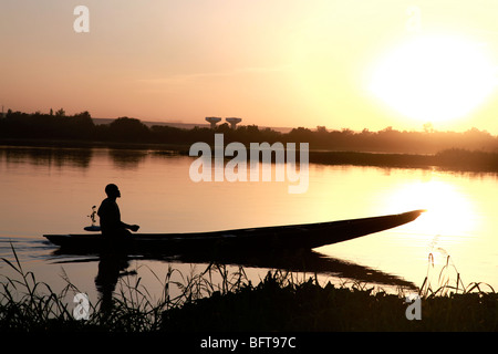 Fisherman in a small boot crossing a river at sunset - Stock Photo