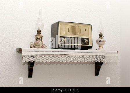 Antique radio on the wall with two old traditional lamps - Stock Photo