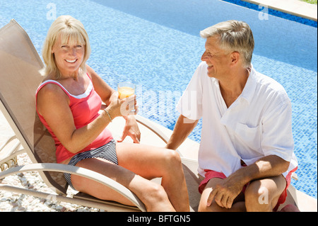 A senior couple by the pool - Stock Photo
