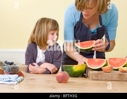 girl and mother with watermelon slices - Stock Photo