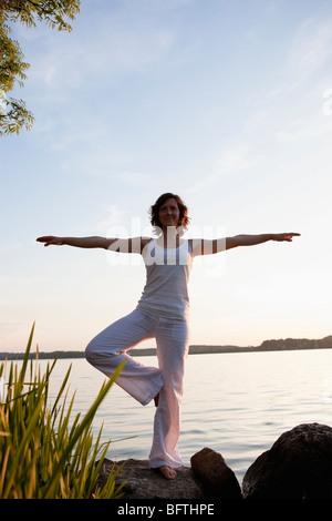 Woman Performing Yoga At Lakeside - Stock Photo