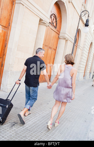 couple with trolly walking along street - Stock Photo
