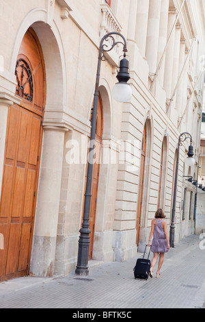 woman with trolly walking along street - Stock Photo