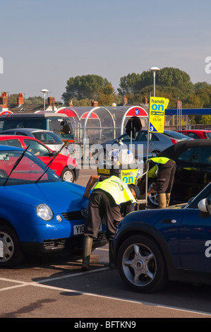 Men washing cars for the Hands On car wash outside the Tesco Superstore supermarket in Beccles,Suffolk,Uk - Stock Photo