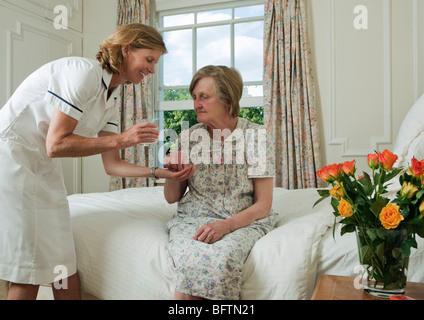 Elderly woman taking pill from nurse - Stock Photo