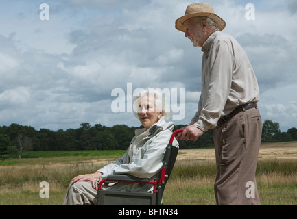 Elderly man pushing woman in wheelchair - Stock Photo
