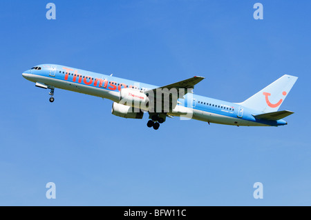 Boeing 757 operated by Thomson Airways climbing out from take off at Birmingham Airport, UK. - Stock Photo