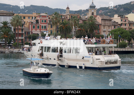 A cruise boat with tourists on board is mooring to the pier in Santa Margherita Ligure, Italy. - Stock Photo