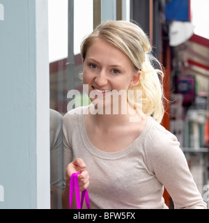 young woman next to a shop window - Stock Photo