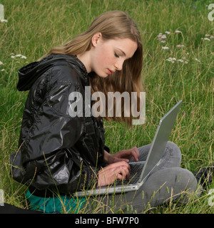young woman with laptop in the park - Stock Photo