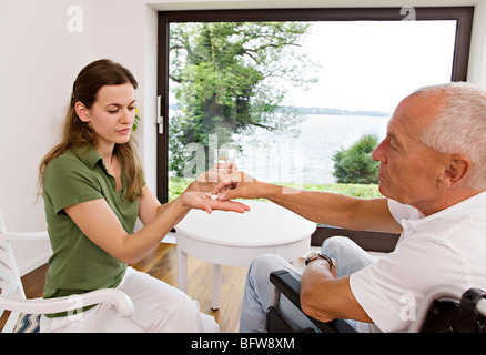 woman handing medicine to man - Stock Photo