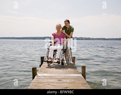 woman and senior woman in wheelchair - Stock Photo