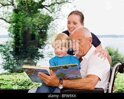 senior man reading book to boy - Stock Photo