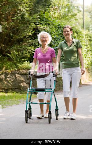 woman walking with senior woman - Stock Photo