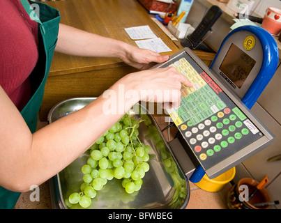 shopkeeper putting fruit on scale - Stock Photo